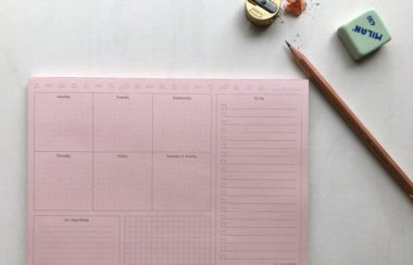 A pink planner pad with a pencil, sharpener and eraser